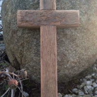 Reclaimed wood cross leaning against a rock