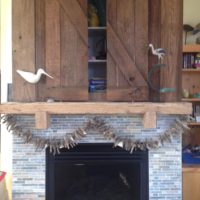 Small reclaimed wood barn doors installed above a fireplace